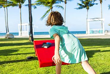 Rear view of 5 year old boy tossing beanbag, Grand Cayman, Cayman Islands