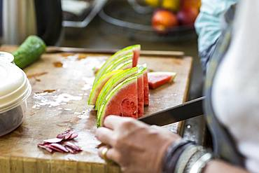close up of hands cutting watermelon slices in kitchen