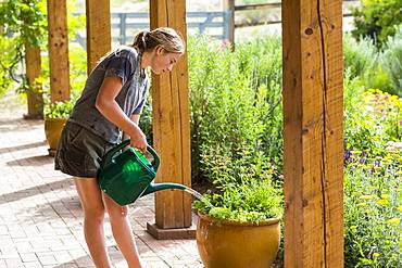 A teenage girl watering plants on porch