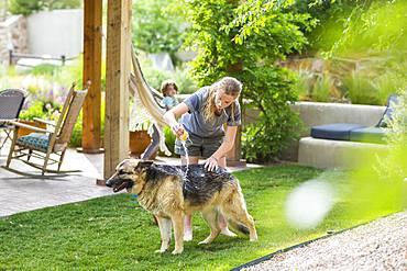 A teenage girl washing her dog on green lawn