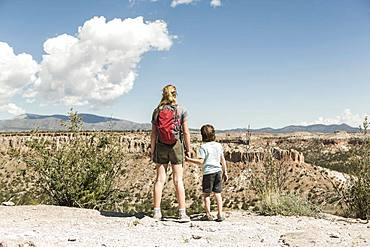 Brother and sister holding hands visiting a prehistoric site in New Mexico