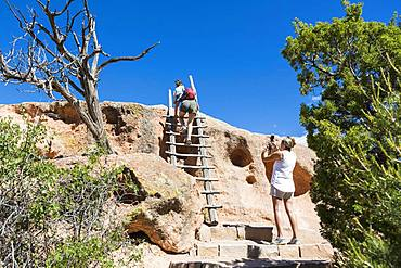 Family exploring the Tsankawi Ruins in New Mexico climbing up steps