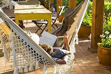 Two people lying in a hammock on a porch reading