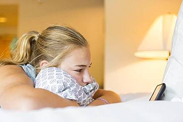 A teenage girl lying on hotel room bed looking at smart phone