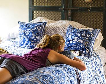 A teenage girl lying on her bed, reading