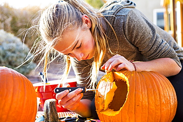 A teenage girl carving a large pumpkin at Halloween