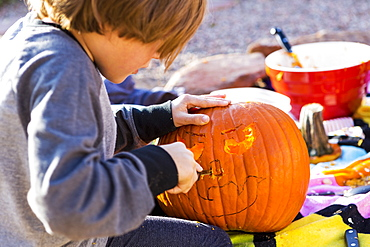 A six year old boy carving pumpkin outdoors at Halloween