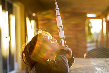 A boy playing with a toy Nasa Saturn 5 rocket, day dreaming about space flight