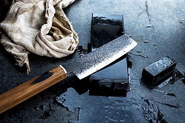 High angle close up of handmade knife on whetstone