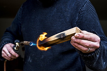Close up of man holding blowtorch, charring wooden handle of a knife