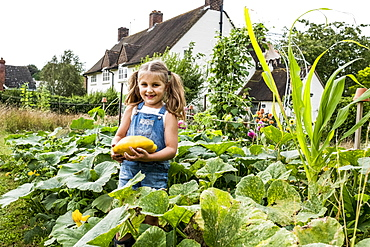 Girl standing in a vegetable patch in a garden, holding yellow gourd, smiling at camera