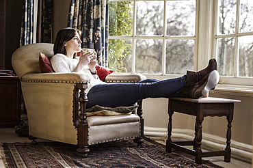 A young woman relaxing at home, with her feet up, having a cup of tea, Ringwood, Hampshire, England