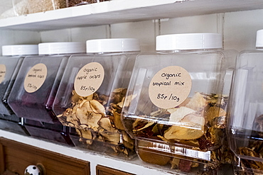 Close up of shelf with a selection of dried fruits in glass jars