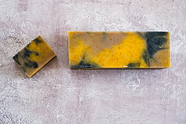 High angle close up of yellow and black homemade bar of soap