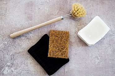 High angle close up of wooden washing up brush, soap and sponges