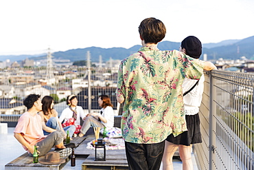 Group of young Japanese men and women on a rooftop in an urban setting, Fukuoka, Kyushu, Japan