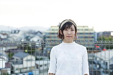Japanese woman standing on a rooftop in an urban setting, looking at camera, Fukuoka, Kyushu, Japan