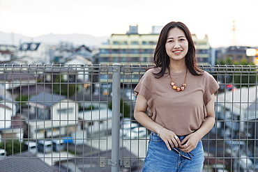 Young Japanese woman standing on a rooftop in an urban setting, looking at camera, Fukuoka, Kyushu, Japan