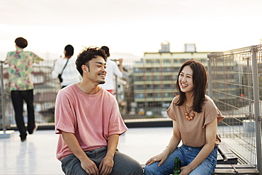 Smiling young Japanese man and woman sitting on a rooftop in an urban setting, Fukuoka, Kyushu, Japan