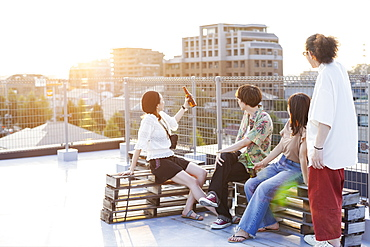 Group of young Japanese men and women sitting on a rooftop in an urban setting, Fukuoka, Kyushu, Japan