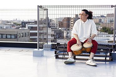 Japanese man sitting on a rooftop in an urban setting, playing drums, Fukuoka, Kyushu, Japan
