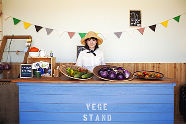 Japanese woman wearing hat standing behind counter in a farm shop, smiling at camera, Kyushu, Japan