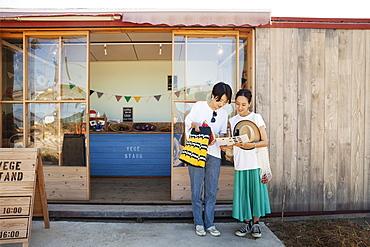 Two smiling Japanese women standing outside a farm shop, Kyushu, Japan