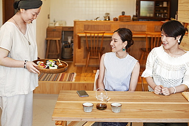 Japanese woman serving two female customers in a vegetarian cafe, Kyushu, Japan