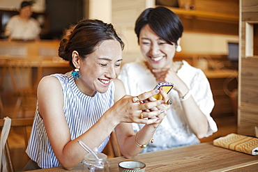 Two Japanese women sitting at a table in a vegetarian cafe, using mobile phone, Kyushu, Japan
