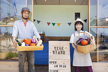 Japanese man and woman standing outside a farm shop, holding crate and basket with fresh vegetables, looking at camera, Kyushu, Japan