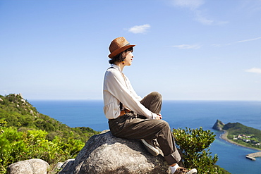 Japanese woman wearing hat sitting on a rock on cliff, ocean in the background, Kyushu, Japan
