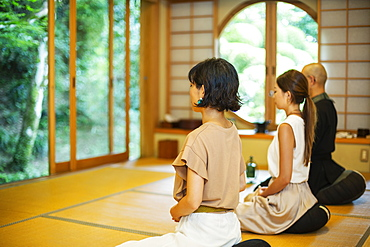 Two Japanese women and Buddhist priest kneeling in Buddhist temple, praying, Kyushu, Japan