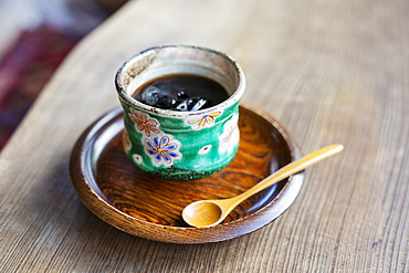 High angle close up of Japanese condiment in green bowl on wooden plate, Kyushu, Japan