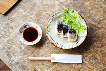High angle close up of plate of Sushi and bowl of Soy Sauce on a table in Japanese restaurant, Kyushu, Japan