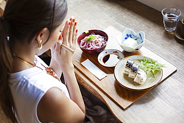 High angle view of Japanese woman sitting at a table in a Japanese restaurant, eating, Kyushu, Japan