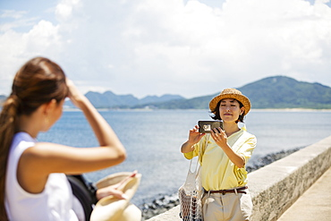 Two Japanese women standing by the ocean, taking picture with mobile phone, Kyushu, Japan