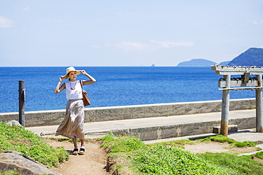 Japanese woman wearing hat walking along path by the ocean, Kyushu, Japan