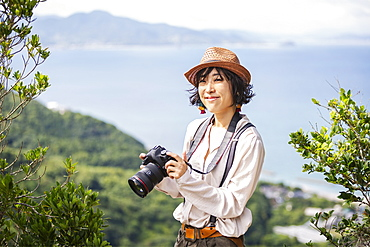 Japanese woman wearing hat and carrying backpack and camera standing on a cliff, ocean in the background, Kyushu, Japan