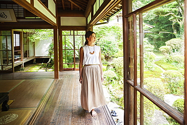 Japanese woman standing in Buddhist temple, Kyushu, Japan