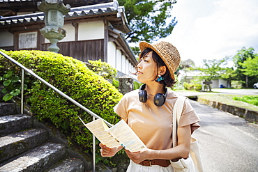 Japanese woman wearing hat and holding map standing outside Buddhist temple, Kyushu, Japan
