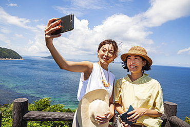 Two Japanese women wearing hats standing on a cliff, taking selfie with mobile phone, ocean in the background, Kyushu, Japan