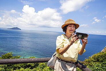Japanese woman wearing hat standing on a cliff, taking selfie with mobile phone, ocean in the background, Kyushu, Japan