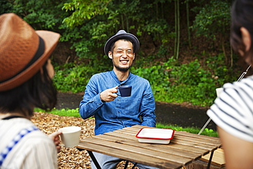 Japanese man and two women sitting outdoors at a table, drinking coffee, Kyushu, Japan