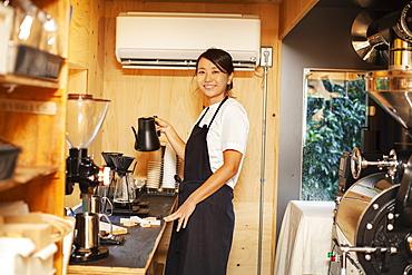 Japanese woman wearing apron standing in an Eco Cafe, preparing coffee, smiling at camera, Kyushu, Japan