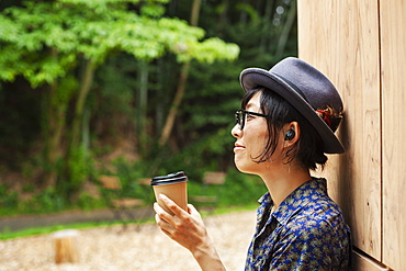 Japanese woman wearing glasses and hat standing outside Eco Cafe, holding paper cup, Kyushu, Japan