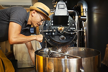 Japanese man wearing hat and glasses standing in an Eco Cafe, operating coffee roaster machine, Kyushu, Japan