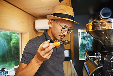 Japanese man wearing hat and glasses standing in an Eco Cafe, smelling freshly roasted coffee beans, Kyushu, Japan