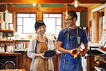 Smiling Japanese woman and man wearing blue apron and glasses standing in a leather shop, Kyushu, Japan