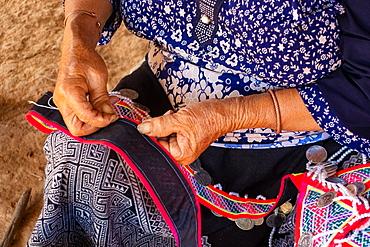 Woman seated stitching, making traditional garments, Vang Vieng, Laos, Laos