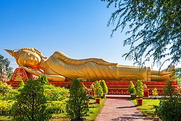 Golden Reclining Buddha in gardens at Wat Pha That Luang Vientiane Laos, Laos